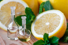 Essential oils. Essential oil in glass bottle with fresh, juicy lemon fruit and green leaves of mint-beauty treatment. Spa concept. Selective focus Stock Image
