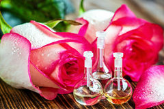 Essential oils. Essential oil in glass bottle with rose flowers and petals on wooden background. Beauty treatment. Spa concept. Selective focus Stock Image