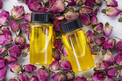 Essential oils. With rose buds on the table stock image