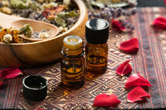 Essential oils with roses and herbs. Essential oils with rose flowers and dried herbs Stock Photos