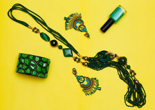 Essentials fashion woman objects on yellow background Female accessories: green bracelet earrings bead. top view flat lay royalty free stock photography