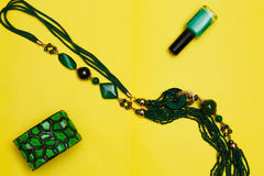 Essentials fashion woman objects on yellow background Female accessories: green bracelet earrings bead. top view flat lay. Essentials fashion woman objects on Royalty Free Stock Images