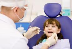 Essere dato d'esame dentario alla bambina dal dentista immagine stock