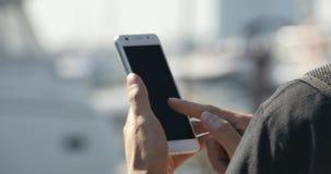 essere umano di 4k A che utilizza uno smartphone alla spiaggia, all'yacht & alla navigazione nel porto archivi video