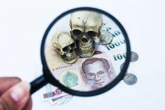 Essere umano e soldi del cranio in lente d'ingrandimento Fotografia Stock
