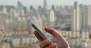 essere umano 4k che per mezzo di uno smartphone contro il fondo urbano moderno della costruzione archivi video