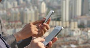 essere umano 4k che per mezzo di uno smartphone contro il fondo urbano moderno della costruzione stock footage