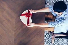 Essere umano maschio giovane che tiene un regalo attuale con il nastro rosso nel fondo di legno Fotografia Stock