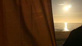 Essere umano in tende di chiusura di mas del gas alle siluette piacevoli di vista del mare stock footage