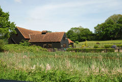 Essex barn conversion. Lovely old essex barn conversion with a reedy pond in the foreground and a paddock in the background royalty free stock photos