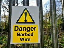 Essex, Reino Unido - 1º de abril de 2019: Sinal em uma cerca, advertência do arame farpado do perigo do perigo imagens de stock royalty free