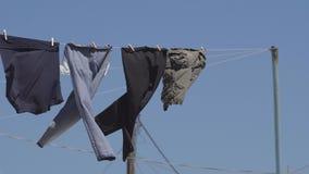 Essiccazione della lavanderia su una corda da bucato fuori al sole archivi video