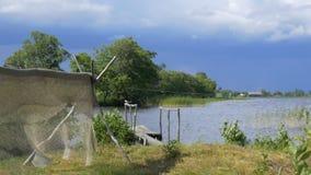 Essiccazione della rete da pesca nel vento sui pali su terra di secchezza stock footage
