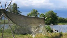 Essiccazione della rete da pesca nel vento sui pali su terra di secchezza video d archivio