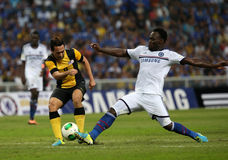 Essien micheal. SHAH ALAM - JULY 21: Chelsea Football Club player Michael Essien (white jersey) tackles a Malaysian player Norsharul Talaha (yellow) in a Stock Photos