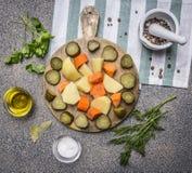 In Essig eingelegte Gurken, Kartoffeln, Karotten und Gewürz mit Draufsichtabschluß des Hintergrundes der Kräuter hölzernem rustik Lizenzfreies Stockbild