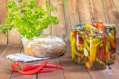 In Essig eingelegte Paprika-Pfeffer im Glasgefäß mit frischen Paprikas, Brot und stockbild