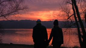 Essonne France a couple walks at sunset in december. A men and a women in front of a lake with a beautiful orange sky and silhouette of autumn trees in stock image
