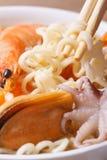 Essstäbchen halten die chinesischen Nudeln in der Suppe von den Meeresfrüchten Lizenzfreie Stockbilder