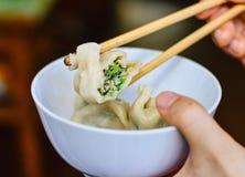 Essstäbchen heben einen geöffneten chinesischen Mehlkloß von einer Schüssel auf Lizenzfreie Stockfotografie