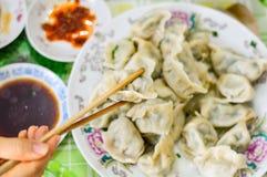 Essstäbchen heben Mehlklöße Boilded Chineses auf Stockfotos