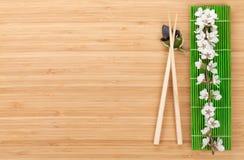 Essstäbchen und Kirschblüte-Niederlassung über Bambusmatte Stockbilder