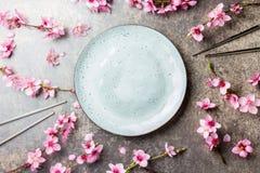 Essstäbchen und Kirschblüte-Niederlassungen auf grauem Steinhintergrund japanisches Lebensmittelkonzept Draufsicht, Kopienraum Stockbilder