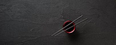 Essstäbchen und Schüssel mit Sojasoße auf schwarzem Hintergrund Stockfotografie
