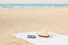 Essuie-main blanc sur la plage avec les lunettes de soleil et le chapeau Photographie stock