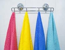 Essuie-main colorés s'arrêtant dans une salle de bains Photo stock