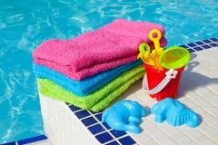 Essuie-main et jouets en plastique près du regroupement de bain Photos stock