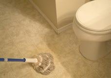 A essuyé le plancher carrelé par salle de bains avec le balai images stock