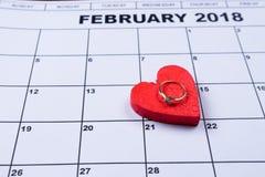 Está 14 de febrero un corazón decorativo en él anillo de compromiso con el diamante Imagen de archivo