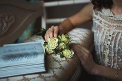 Está sosteniendo las rosas blancas de un ramo en las manos de la muchacha Fotos de archivo