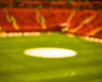 Estádio verde vermelho vazio do campo de futebol do futebol Foco macio fundo borrado foto de stock