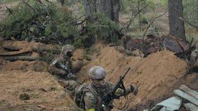 Están encendiendo a los soldados en camuflaje con las armas del combate en el refugio del bosque, el concepto militar metrajes