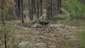 Están encendiendo a los soldados en camuflaje con las armas del combate en el refugio del bosque, el concepto militar almacen de metraje de vídeo