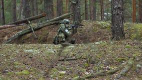 Están encendiendo a los soldados en camuflaje con las armas del combate en el refugio del bosque, el concepto militar almacen de video