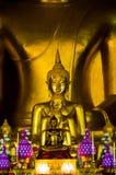 Estátua amarela dourada da Buda que senta-se que medita e que reza foto de stock royalty free