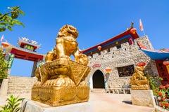 Estátua chinesa do leão do ouro e parede de pedra de estilo chinês fotos de stock royalty free