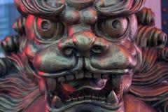 Estátua chinesa do leão O close-up do focinho à vista da cidade na noite Imagens de Stock