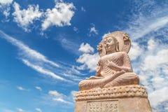 Estátua cinzelada da Buda do arenito no fundo do céu azul Fotografia de Stock Royalty Free