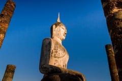 Estátua da Buda cercada pelos polos de pedra Fotos de Stock Royalty Free