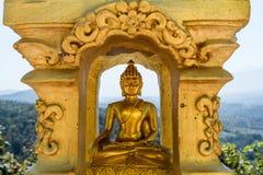 Estátua da Buda do ouro na posição de lótus que medita o rebaixo dourado interno Fotografia de Stock Royalty Free