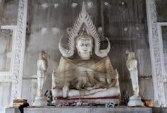 Estátua da Buda envolvida no celofane no templo budista sob a construção Imagem de Stock