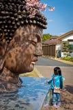 A estátua da cabeça do ` s da Buda com uma criança em Japão fotografia de stock