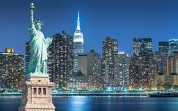 A estátua da liberdade com arquitetura da cidade em Manhattan na noite, New York City fotografia de stock royalty free
