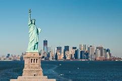 A estátua da liberdade contra a skyline de New York City Imagens de Stock Royalty Free