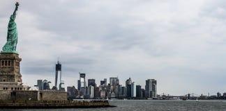 A estátua da liberdade, Lower Manhattan, NYC e ponte de Brooklyn imagem de stock royalty free