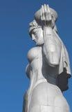 Estátua de alumínio de uma mulher no vestuário Georgian tradicional - abraço imagem de stock royalty free